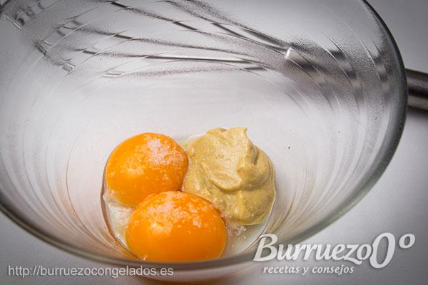 Yemas de huevo, mostaza, sal y pimienta, en un cuenco.